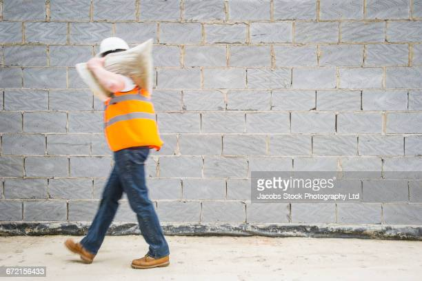 caucasian construction worker carrying sack - bauarbeiter stock-fotos und bilder