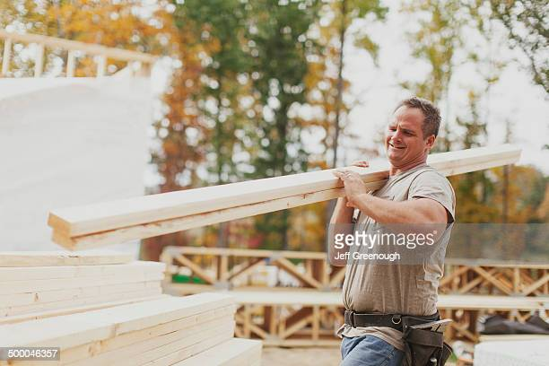Caucasian construction worker carrying wood planks