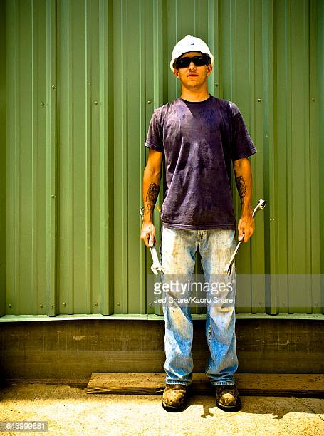 Caucasian construction worker holding wrenches on work site