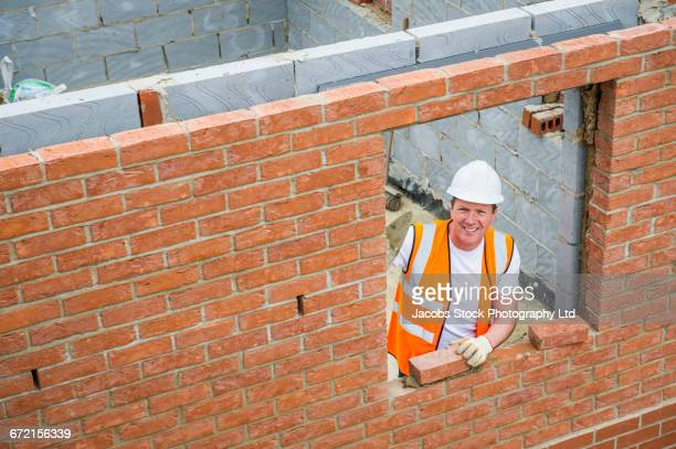 caucasian construction worker laying bricks with mortar - spalding england stock photos and pictures