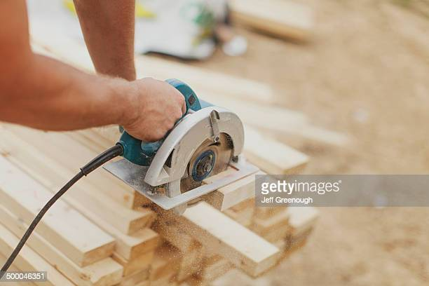 Caucasian construction worker sawing wood planks