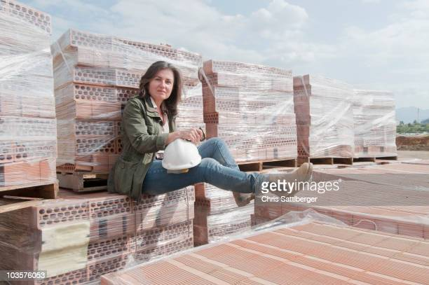 Caucasian construction worker sitting on stack of bricks
