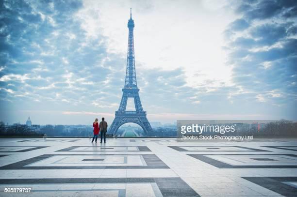 Caucasian couple admiring Eiffel Tower, Paris, Ile-de-France, France