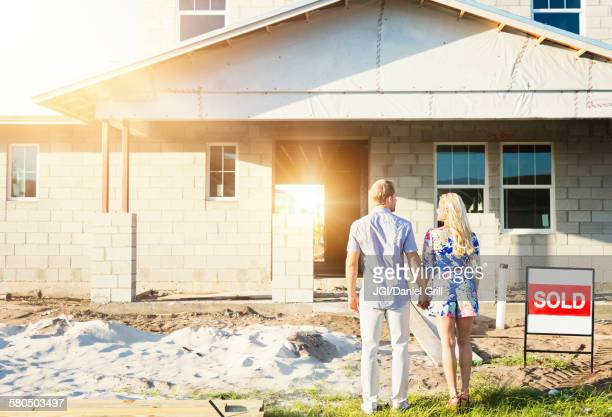 Caucasian couple admiring new home