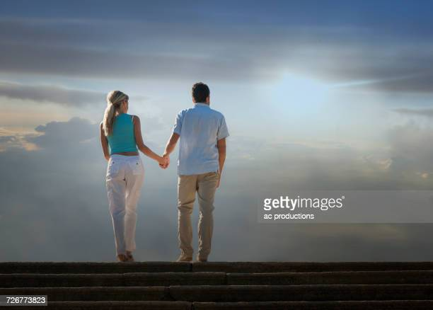 caucasian couple admiring scenic view of clouds from staircase - 中年カップル ストックフォトと画像