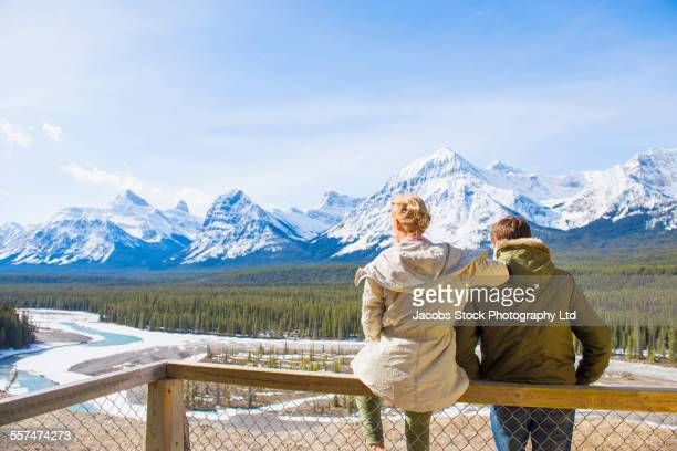 Caucasian couple admiring scenic view of snowy forest and mountains, Banff, Alberta, Canada