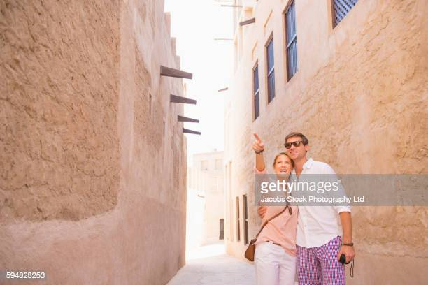 Caucasian couple admiring view in alley