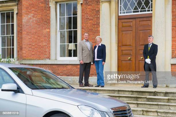 Caucasian couple and butler smiling outside mansion