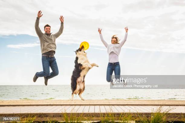 Caucasian couple and dog jumping for joy on boardwalk