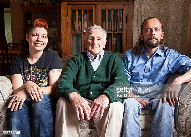 Caucasian couple and older man smiling on sofa