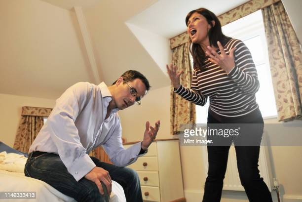 caucasian couple arguing in bedroom - wife stock pictures, royalty-free photos & images