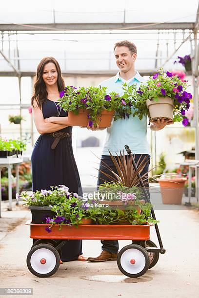 caucasian couple carrying potted flowers in plant nursery - toy wagon stock photos and pictures