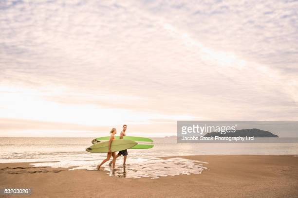 caucasian couple carrying surfboards on beach - whangarei heads stock pictures, royalty-free photos & images