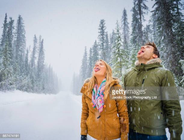 Caucasian couple catching snowflakes on tongues
