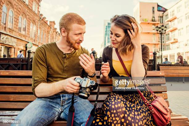 Caucasian couple checking photos on digital camera