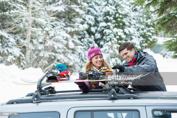 Caucasian couple checking snowboards in car roof rack