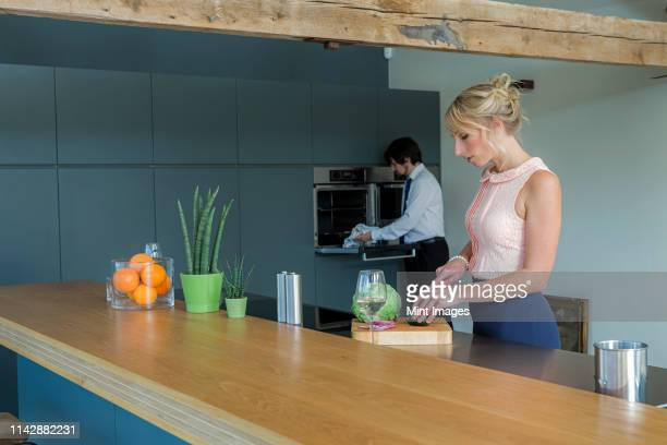 caucasian couple cooking together in kitchen - side view stock pictures, royalty-free photos & images