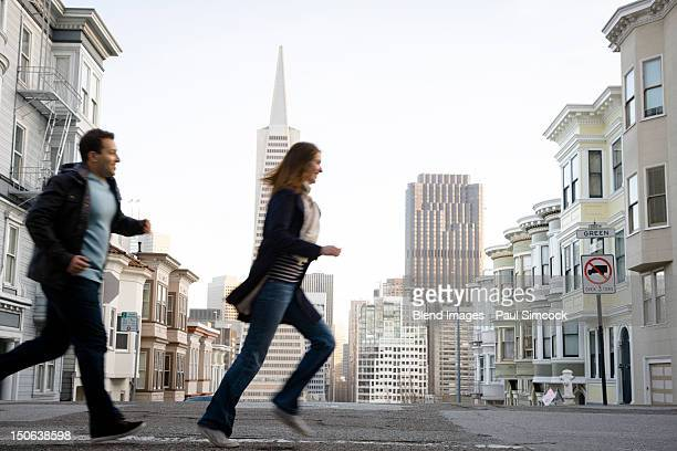 caucasian couple crossing city street - chasing stock pictures, royalty-free photos & images