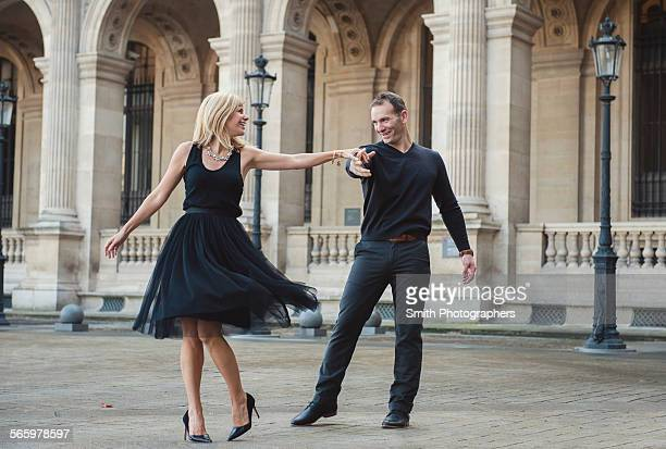 caucasian couple dancing in courtyard - men wearing dresses stock photos and pictures