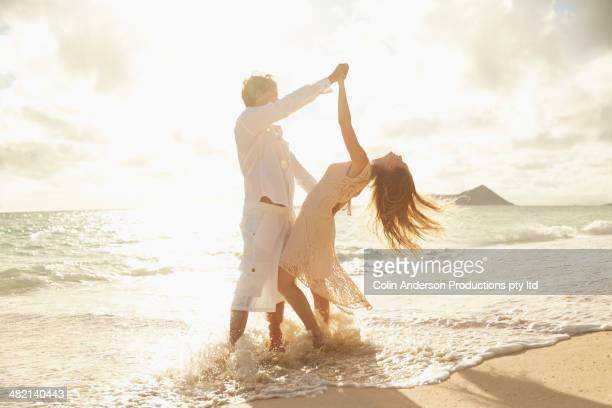 Caucasian couple dancing in surf on beach