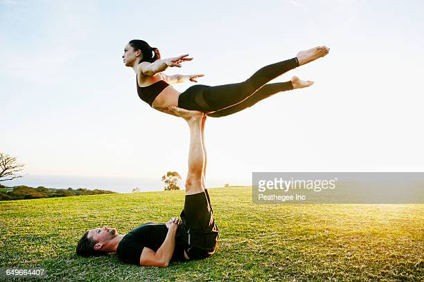 Caucasian couple doing acro yoga in park