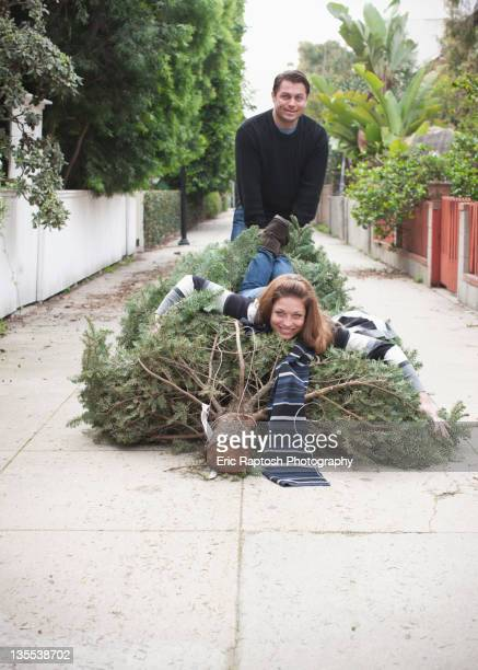 Caucasian couple dragging Christmas tree in alley