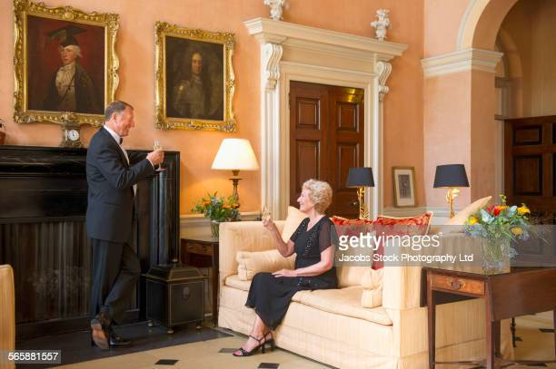 Caucasian couple drinking in mansion formal parlor