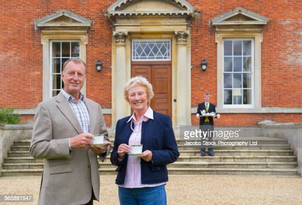 caucasian couple drinking tea outside mansion with butler - butler stock pictures, royalty-free photos & images