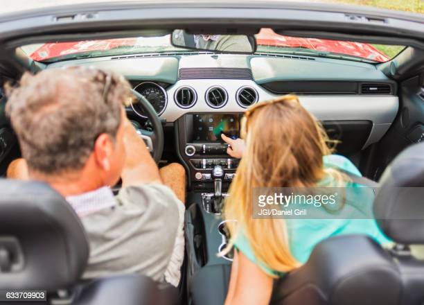 Caucasian couple driving convertible