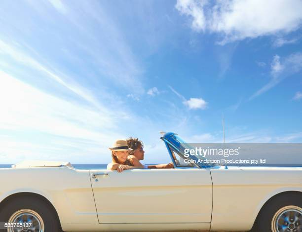 Caucasian couple driving convertible under blue sky