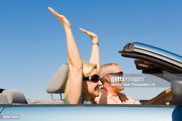 caucasian couple driving convertible under blue sky - travelstock44 stock pictures, royalty-free photos & images