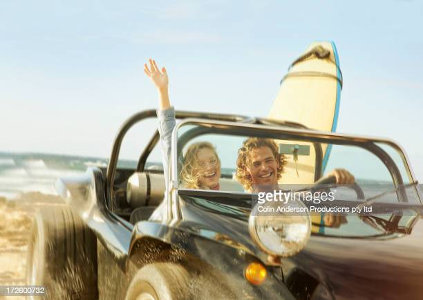 Caucasian couple driving jeep on beach