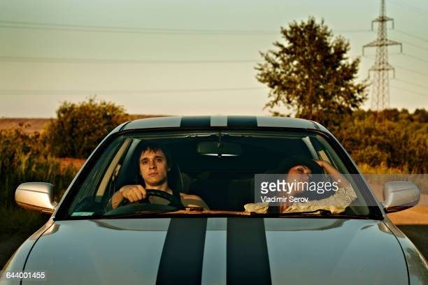 Caucasian couple driving sports car in rural landscape