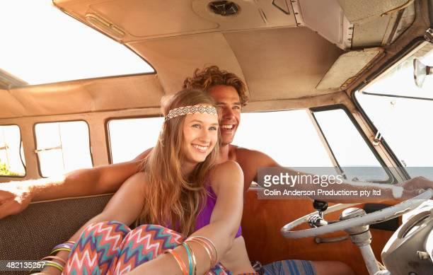 Caucasian couple driving van on beach