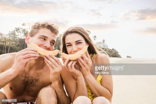 Caucasian couple eating fruit on beach