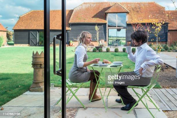 caucasian couple eating lunch in backyard - garden decking stock pictures, royalty-free photos & images