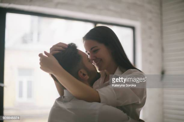 Caucasian couple embracing near window