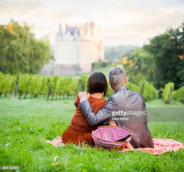 Caucasian couple enjoying picnic in vineyard