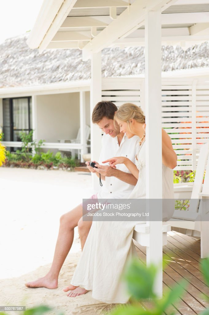 Caucasian couple examining photos on camera on porch railing : Foto stock