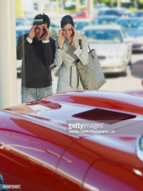 Caucasian couple examining sports car for sale in dealership