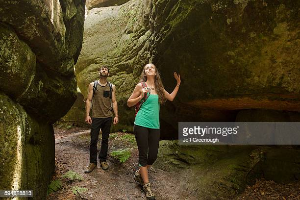caucasian couple exploring cave - cave stock pictures, royalty-free photos & images
