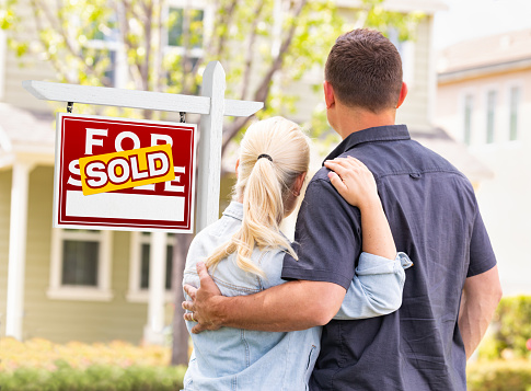 Caucasian Couple Facing Front of Sold Real Estate Sign and House 960627818