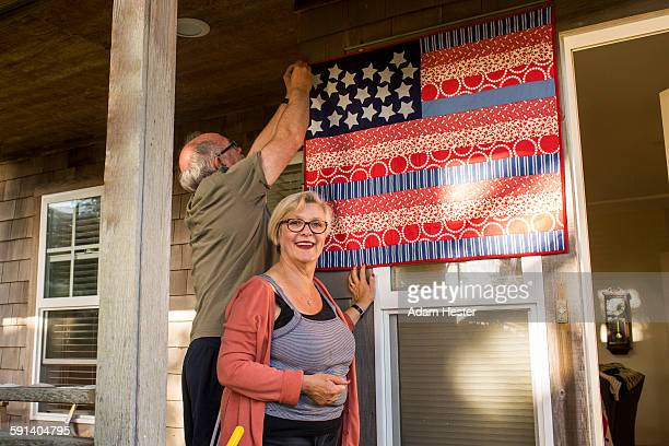 Caucasian couple hanging homemade American flag on porch