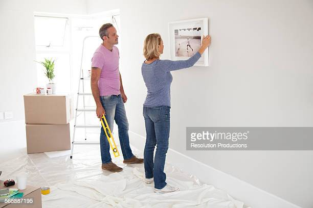 Caucasian couple hanging picture in new home