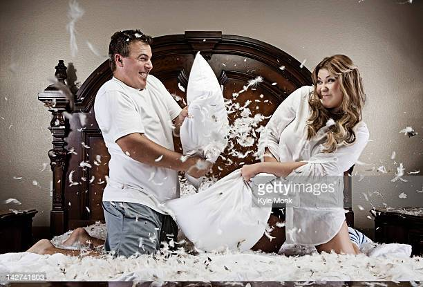 Caucasian couple having pillow fight