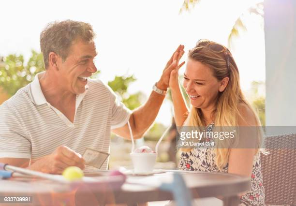 caucasian couple high-fiving at outdoor table - charging sports stock pictures, royalty-free photos & images