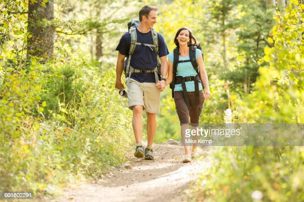 Caucasian couple hiking on path