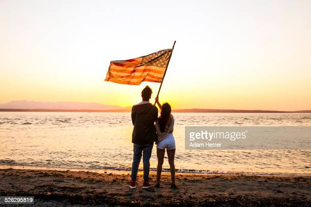 Caucasian couple holding American flag on beach