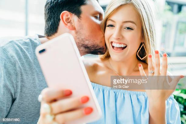 Caucasian couple holding hands and posing for selfie with engagement ring