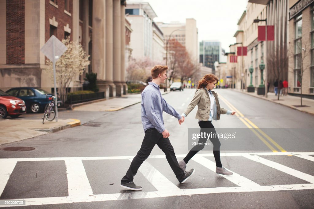 Caucasian couple holding hands crossing city intersection : Stock Photo
